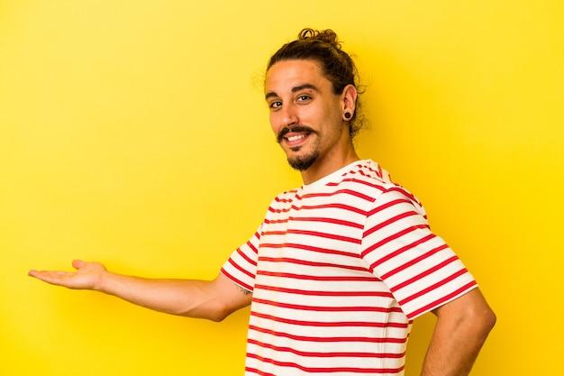 Jovem homem caucasiano com cabelo comprido, isolado em um fundo amarelo, mostrando uma expressão de boas-vindas.