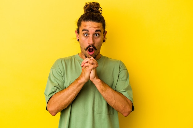 Jovem homem caucasiano com cabelo comprido, isolado em um fundo amarelo, orando por sorte, espantado e abrindo a boca, olhando para frente.