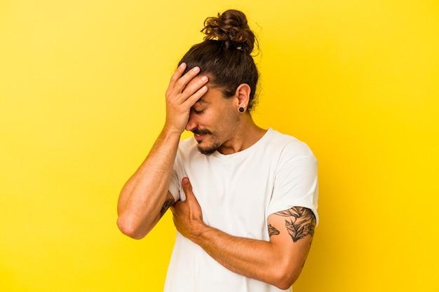 Jovem homem caucasiano com cabelo comprido, isolado em um fundo amarelo pisca para a câmera por entre os dedos, o rosto coberto de vergonha.