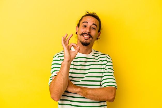 Jovem homem caucasiano com cabelo comprido, isolado em um fundo amarelo pisca um olho e segura um gesto de ok com a mão.