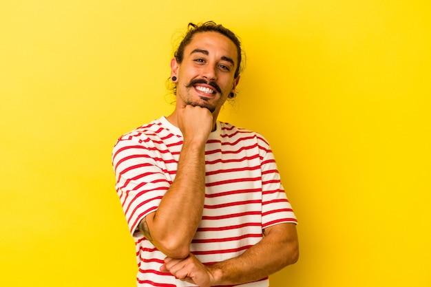Jovem homem caucasiano com cabelo comprido, isolado em um fundo amarelo, sorrindo feliz e confiante, tocando o queixo com a mão.