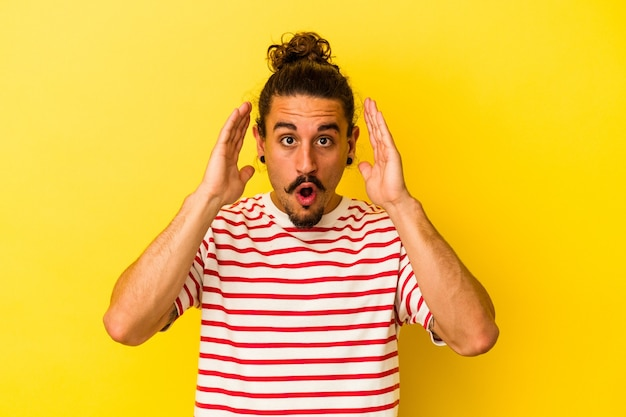 Jovem homem caucasiano com cabelo comprido, isolado em um fundo amarelo, surpreso e chocado.