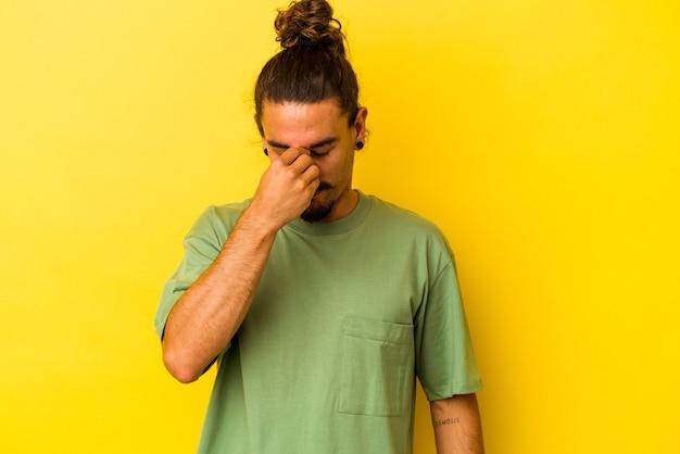 Jovem homem caucasiano com cabelo comprido, isolado em um fundo amarelo, tendo uma dor de cabeça, tocando a frente do rosto.