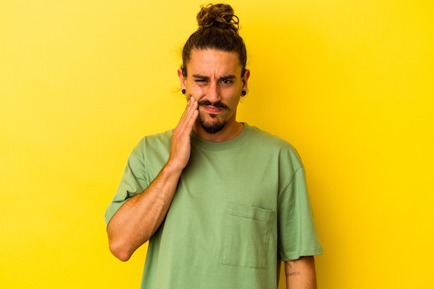 Jovem homem caucasiano com cabelo comprido, isolado em um fundo amarelo, tendo uma forte dor nos dentes, dor molar.