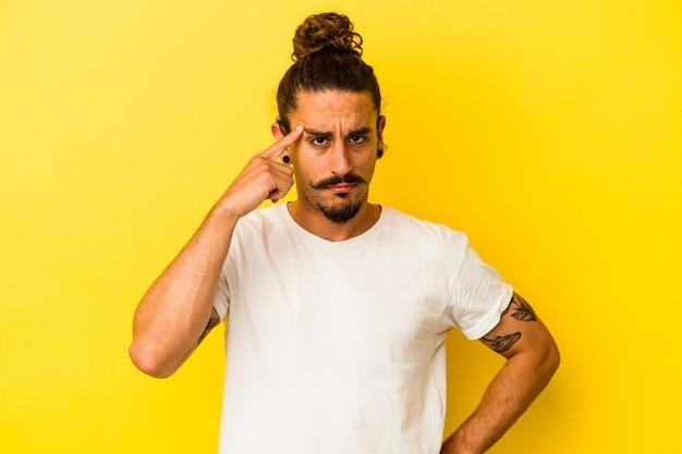 Jovem homem caucasiano com cabelo comprido, isolado no fundo amarelo, apontando o templo com o dedo, pensando, focado em uma tarefa.