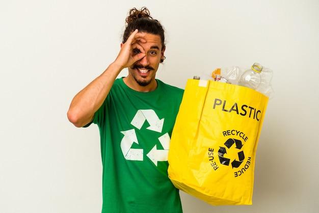 Jovem homem caucasiano com cabelo comprido, reciclagem de plástico isolado no fundo branco, animado, mantendo o gesto ok no olho.