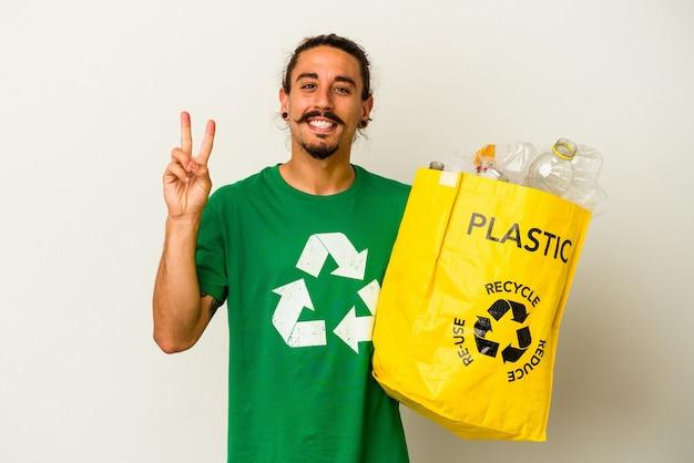 Jovem homem caucasiano com cabelo comprido, reciclagem de plástico isolado no fundo branco, mostrando o número dois com os dedos.