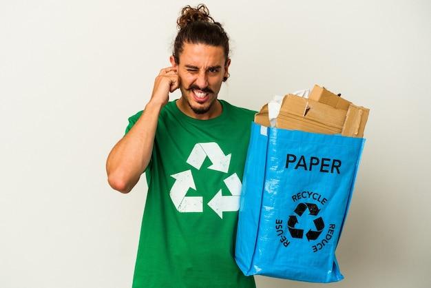Jovem homem caucasiano com cabelo comprido, reciclando papelão isolado no fundo branco, cobrindo as orelhas com as mãos.
