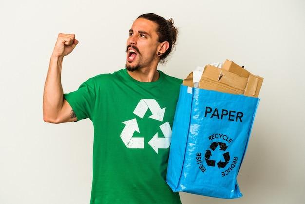 Jovem homem caucasiano com cabelo comprido, reciclando papelão isolado no fundo branco, levantando o punho após uma vitória, o conceito de vencedor.