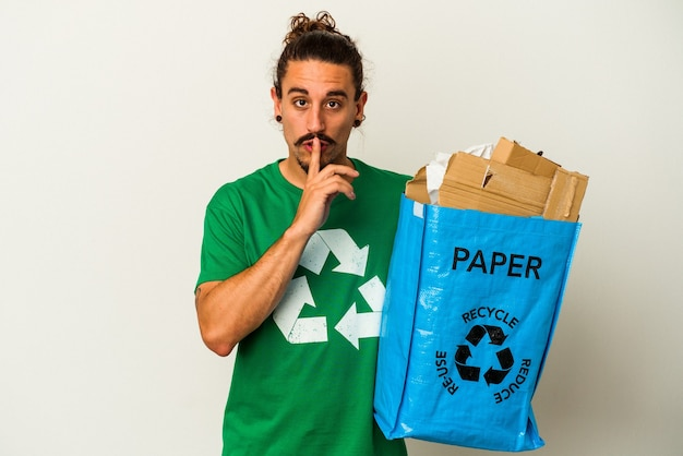 Jovem homem caucasiano com cabelo comprido, reciclando papelão isolado no fundo branco, mantendo um segredo ou pedindo silêncio.