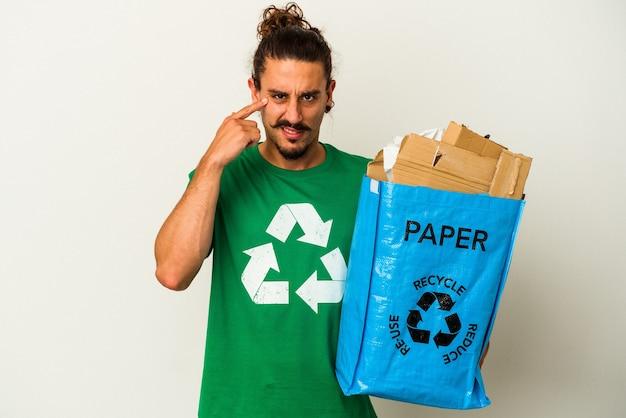Jovem homem caucasiano com cabelo comprido, reciclando papelão isolado no fundo branco, mostrando um gesto de decepção com o dedo indicador.