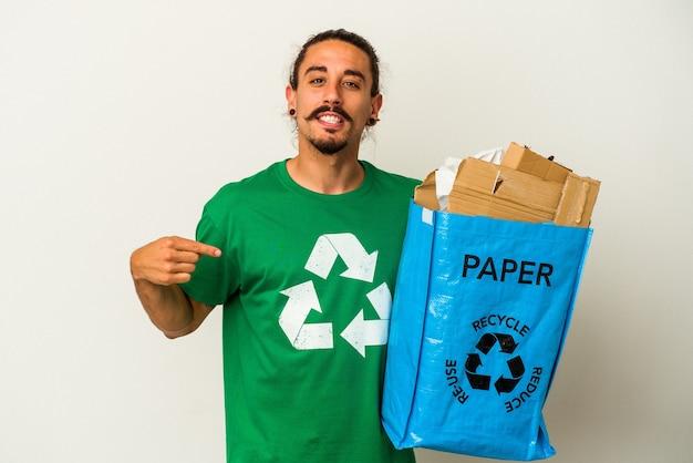 Jovem homem caucasiano com cabelo comprido reciclando papelão isolado no fundo branco pessoa apontando com a mão para um espaço de cópia de camisa, orgulhoso e confiante
