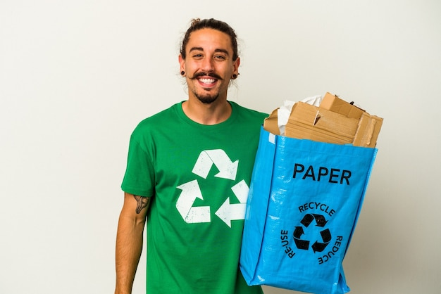 Jovem homem caucasiano com cabelo comprido, reciclando papelão isolado no fundo branco, rindo e se divertindo.