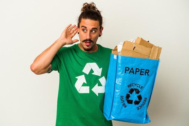 Jovem homem caucasiano com cabelo comprido, reciclando papelão isolado no fundo branco, tentando ouvir uma fofoca.