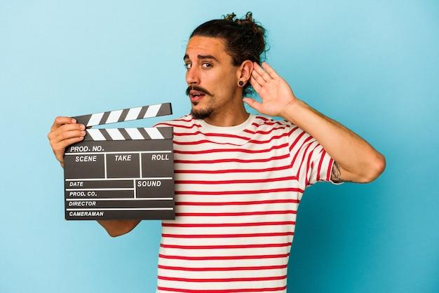 Jovem homem caucasiano com cabelo comprido, segurando claquete isolada em fundo azul, tentando ouvir uma fofoca.