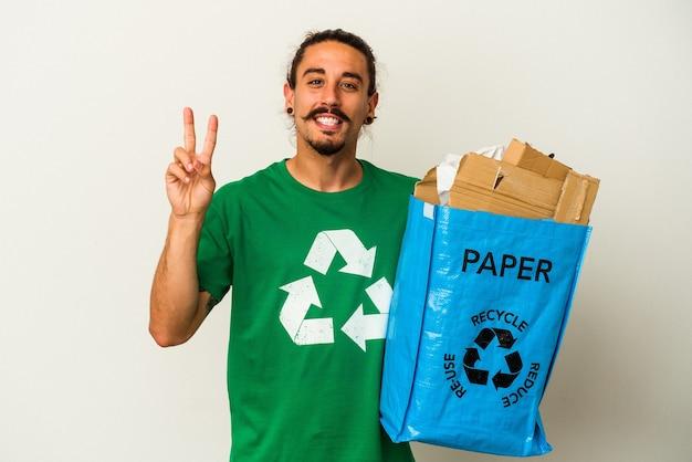 Jovem homem caucasiano com cabelos longos, reciclando papelão isolado no fundo branco, alegre e despreocupado, mostrando um símbolo de paz com os dedos.
