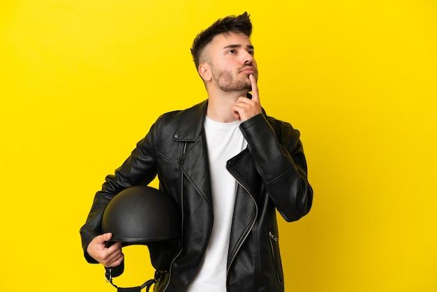 Jovem homem caucasiano com capacete de motociclista isolado em um fundo amarelo, tendo dúvidas enquanto olha para cima