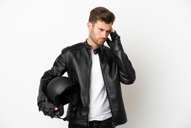 Jovem homem caucasiano com capacete de motociclista isolado no fundo branco com dor de cabeça