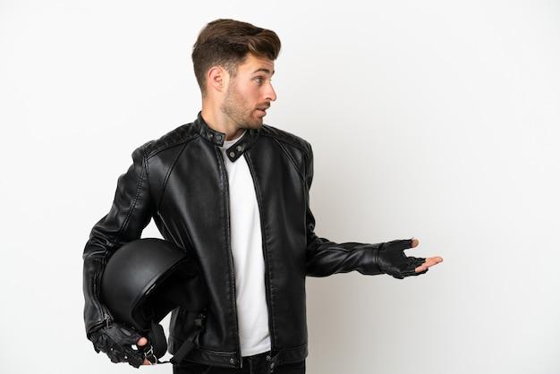 Jovem homem caucasiano com capacete de motociclista isolado no fundo branco com expressão de surpresa ao olhar para o lado