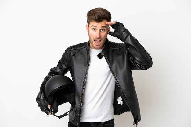 Jovem homem caucasiano com capacete de motociclista isolado no fundo branco com expressão de surpresa