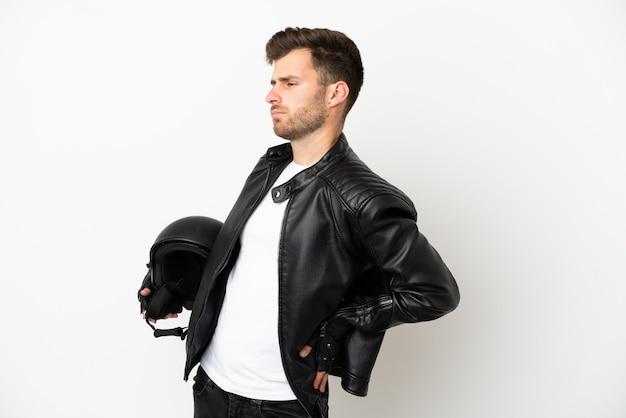 Jovem homem caucasiano com capacete de motociclista isolado no fundo branco, sofrendo de dor nas costas por ter feito um esforço