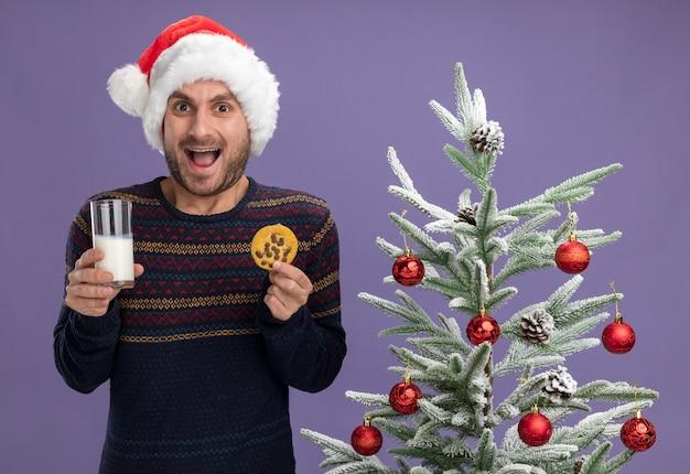 Jovem homem caucasiano com chapéu de natal impressionado em pé perto de uma árvore de natal decorada, segurando um copo de leite e biscoito, olhando para a câmera isolada no fundo roxo