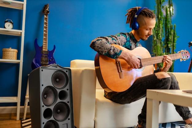 Jovem homem caucasiano com dreadlocks, sentado no sofá e tocar violão