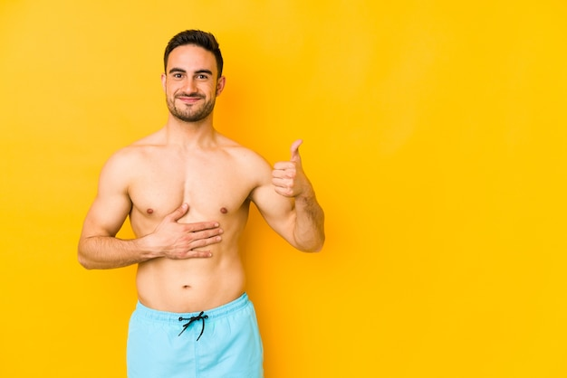 Jovem homem caucasiano com maiô isolado na parede amarela jovem homem caucasiano com trtouches barriga, sorri suavemente, comendo e conceito de satisfação.