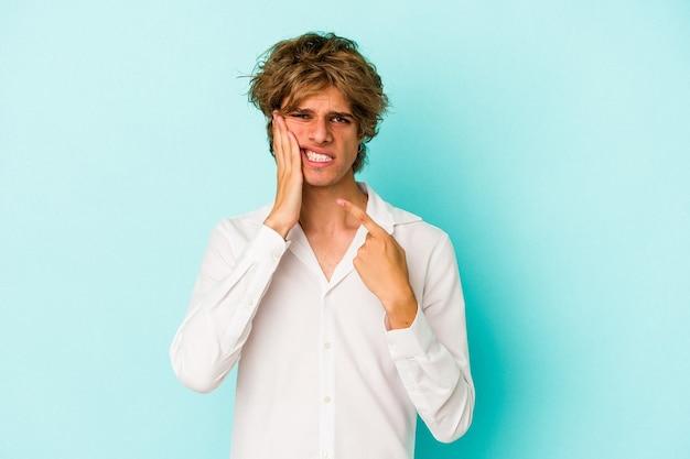 Jovem homem caucasiano com maquiagem isolada em um fundo azul, tendo uma forte dor nos dentes, dor molar.