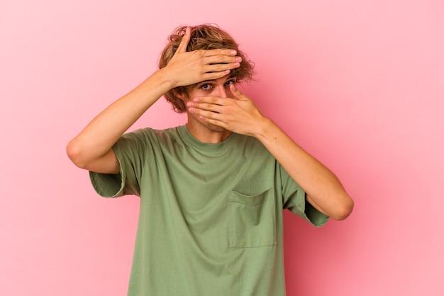 Jovem homem caucasiano com maquiagem isolada no fundo rosa piscar para a câmera através dos dedos, rosto cobrindo vergonha.