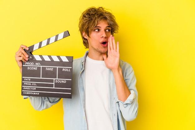 Jovem homem caucasiano com maquiagem segurando claquete isolada em fundo amarelo está contando uma notícia secreta de travagem e olhando para o lado