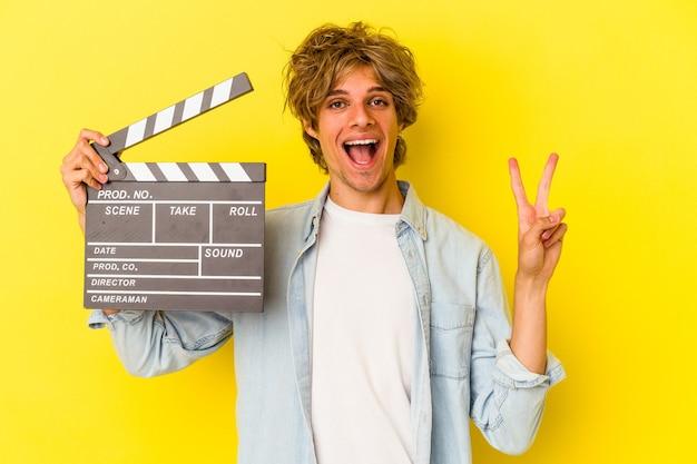 Jovem homem caucasiano com maquiagem segurando claquete isolada em fundo amarelo, mostrando o número dois com os dedos.