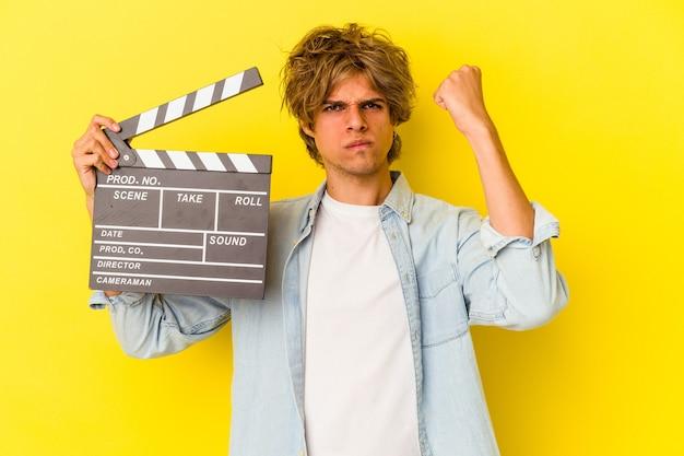 Jovem homem caucasiano com maquiagem segurando claquete isolada em fundo amarelo, mostrando o punho para a câmera, expressão facial agressiva.