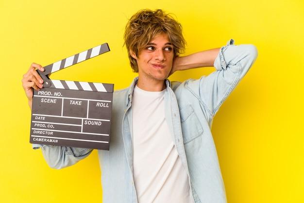 Jovem homem caucasiano com maquiagem segurando claquete isolada no fundo amarelo, tocando a nuca, pensando e fazendo uma escolha.
