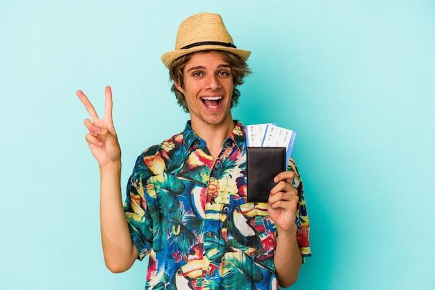 Jovem homem caucasiano com maquiagem segurando o passaporte isolado em um fundo azul, mostrando o número dois com os dedos.