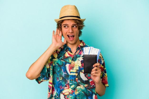Jovem homem caucasiano com maquiagem segurando o passaporte isolado em um fundo azul, tentando ouvir uma fofoca.