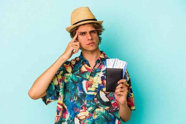 Jovem homem caucasiano com maquiagem, segurando o passaporte isolado no fundo azul, apontando o templo com o dedo, pensando, focado em uma tarefa.