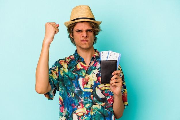 Jovem homem caucasiano com maquiagem segurando o passaporte isolado no fundo azul, mostrando o punho para a câmera, expressão facial agressiva.