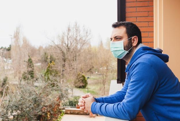 Jovem homem caucasiano com máscara, olhando para o terraço em casa