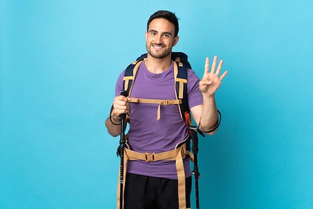 Jovem homem caucasiano com mochila e bastões de trekking isolados em azul feliz e contando quatro com os dedos