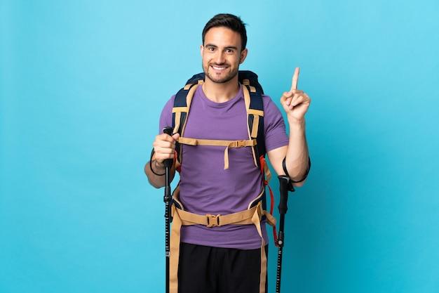 Jovem homem caucasiano com mochila e bastões de trekking isolados em fundo azul, mostrando e levantando um dedo em sinal dos melhores.
