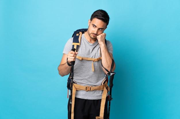Jovem homem caucasiano com mochila e bastões de trekking isolados em um fundo azul com expressão de cansaço e tédio