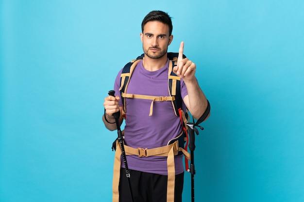 Jovem homem caucasiano com mochila e bastões de trekking isolados na parede azul, contando um com expressão séria