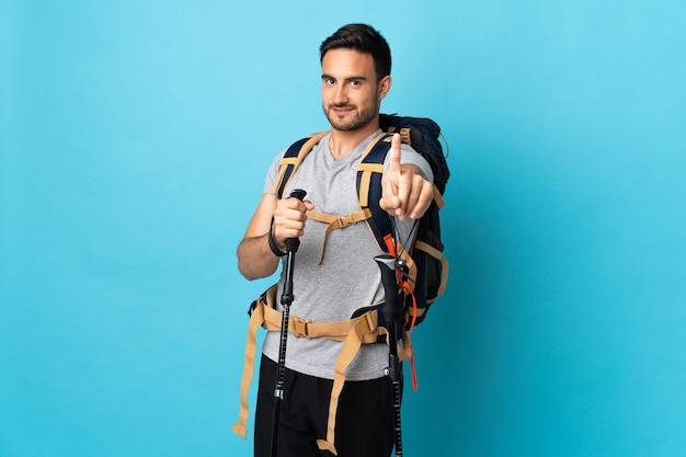 Jovem homem caucasiano com mochila e bastões de trekking isolados na parede azul, mostrando e levantando um dedo