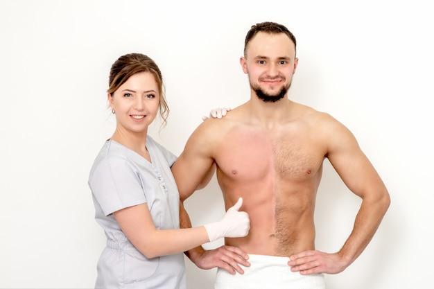 Jovem homem caucasiano com o peito nu antes e depois de depilar o cabelo com o polegar para cima e a mão da esteticista em pé
