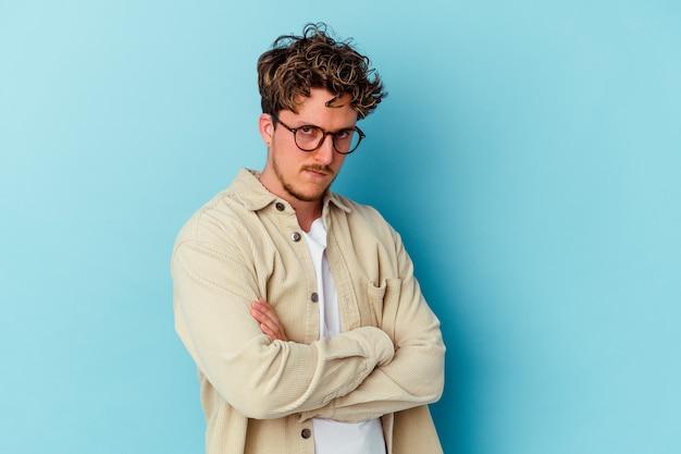 Jovem homem caucasiano com óculos isolados na parede azul, rosto carrancudo e descontente, de braços cruzados
