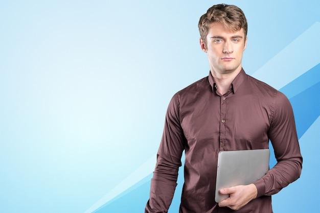 Jovem homem caucasiano com pc portátil nas mãos