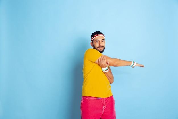 Jovem homem caucasiano com roupas brilhantes, treinando sobre fundo azul conceito de esporte, emoções humanas, expressão facial, estilo de vida saudável, juventude, vendas. fazendo exercícios de alongamento. copyspace.