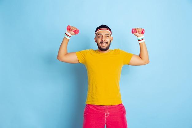 Jovem homem caucasiano com roupas brilhantes, treinando sobre fundo azul conceito de esporte, emoções humanas, expressão facial, estilo de vida saudável, juventude, vendas. treinar com os pesos coloridos. copyspace.