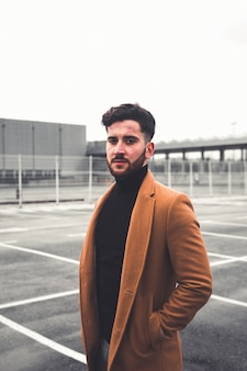 Jovem homem caucasiano com roupas casuais em um estacionamento